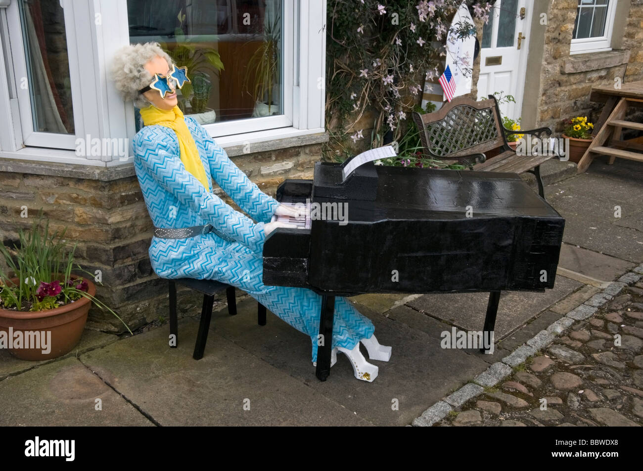 A model of Elton John playing the piano - Stock Image