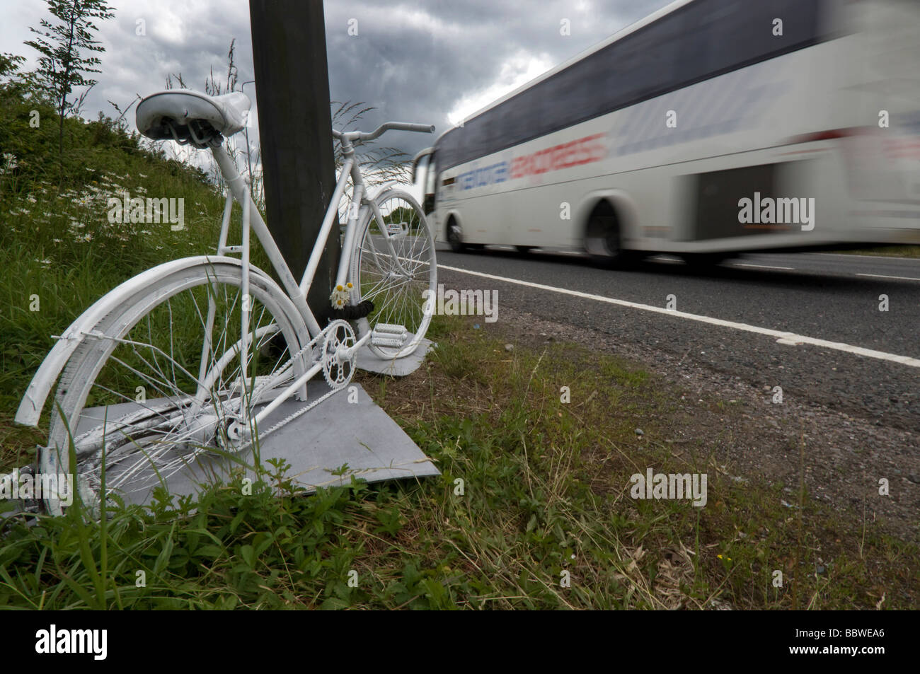 A Ghost Bike - a white painted cycle chained to the spot where a cyclist was killed in a road accident on the A23. - Stock Image
