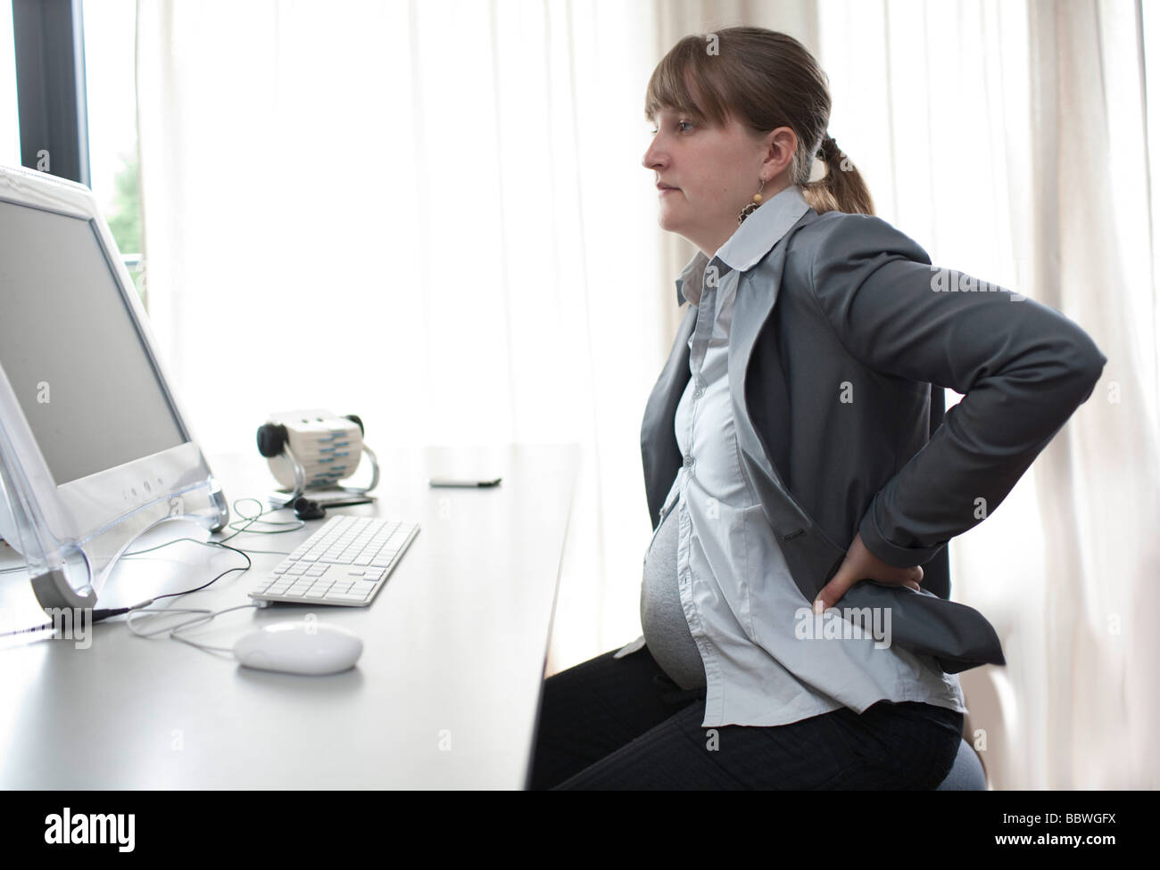 Pregnant woman working at a computer - Stock Image