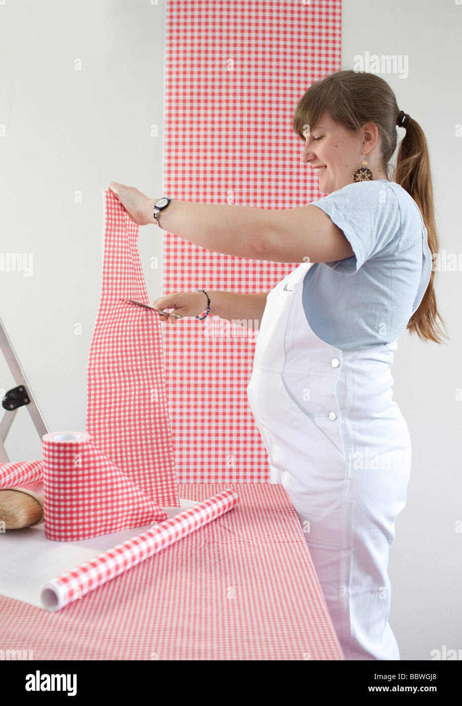 Pregnant woman is paperhanging Stock Photo