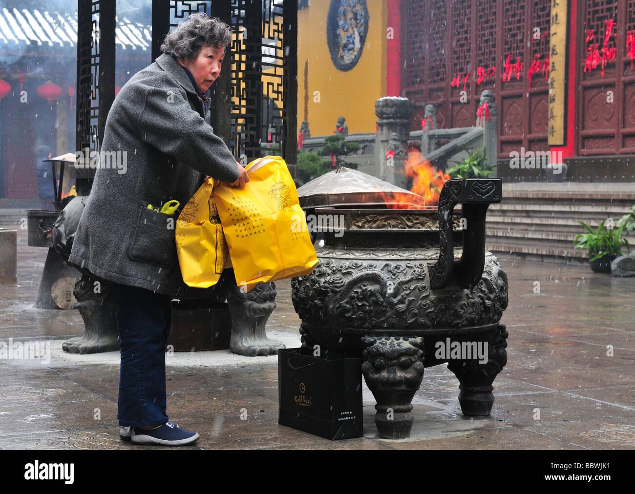 worshiper in Chinese buddhist shrine in the city of Shanghai China - Stock Image