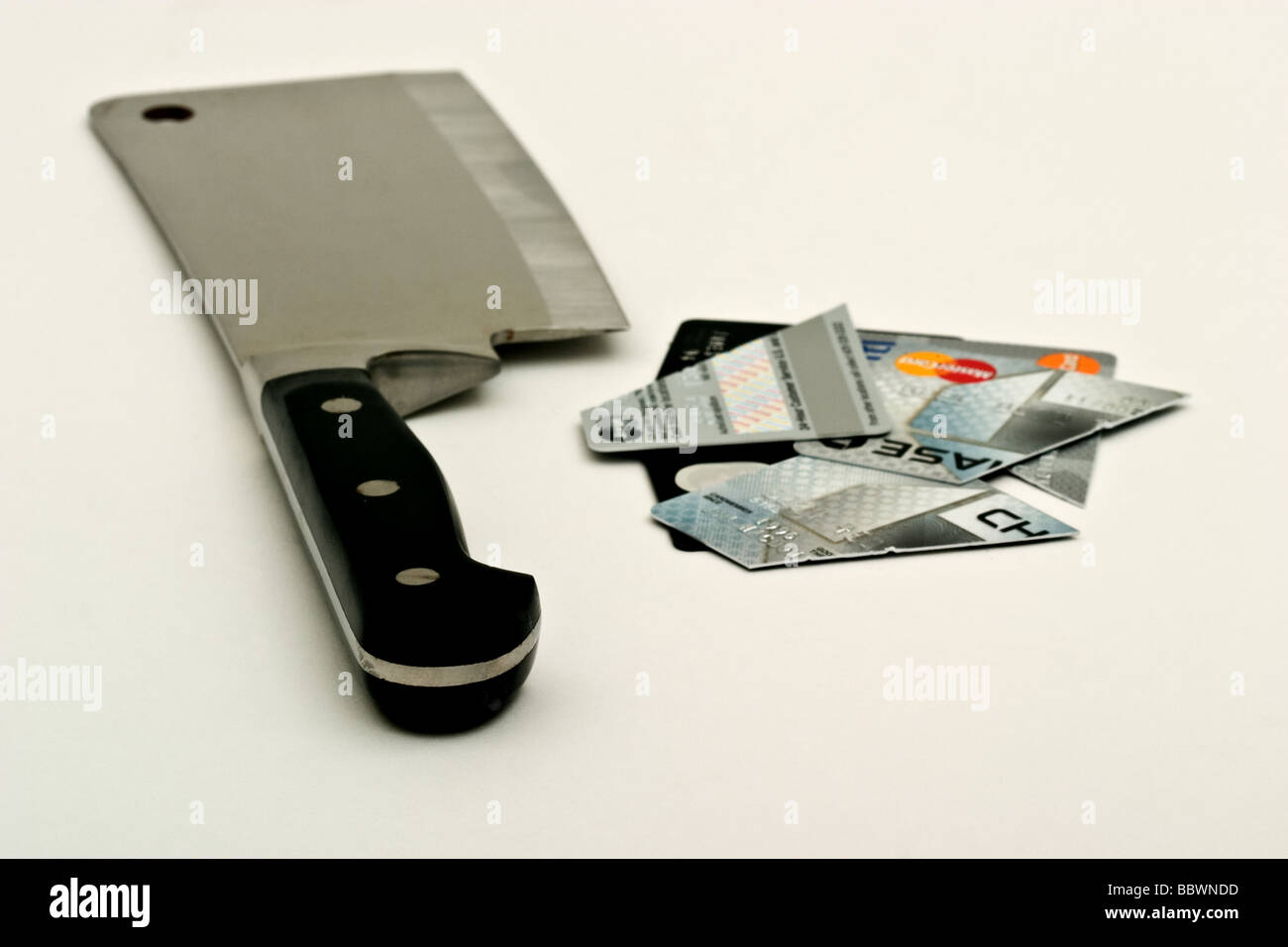 Large metal meat cleaver by a pile of chopped up credit cards - Stock Image