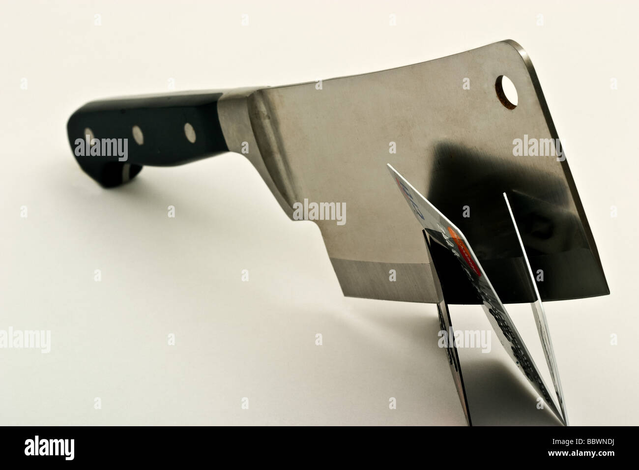 Large metal meat cleaver cutting three credit cards - Stock Image