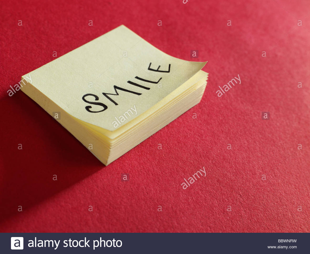 post it note smile red background - Stock Image