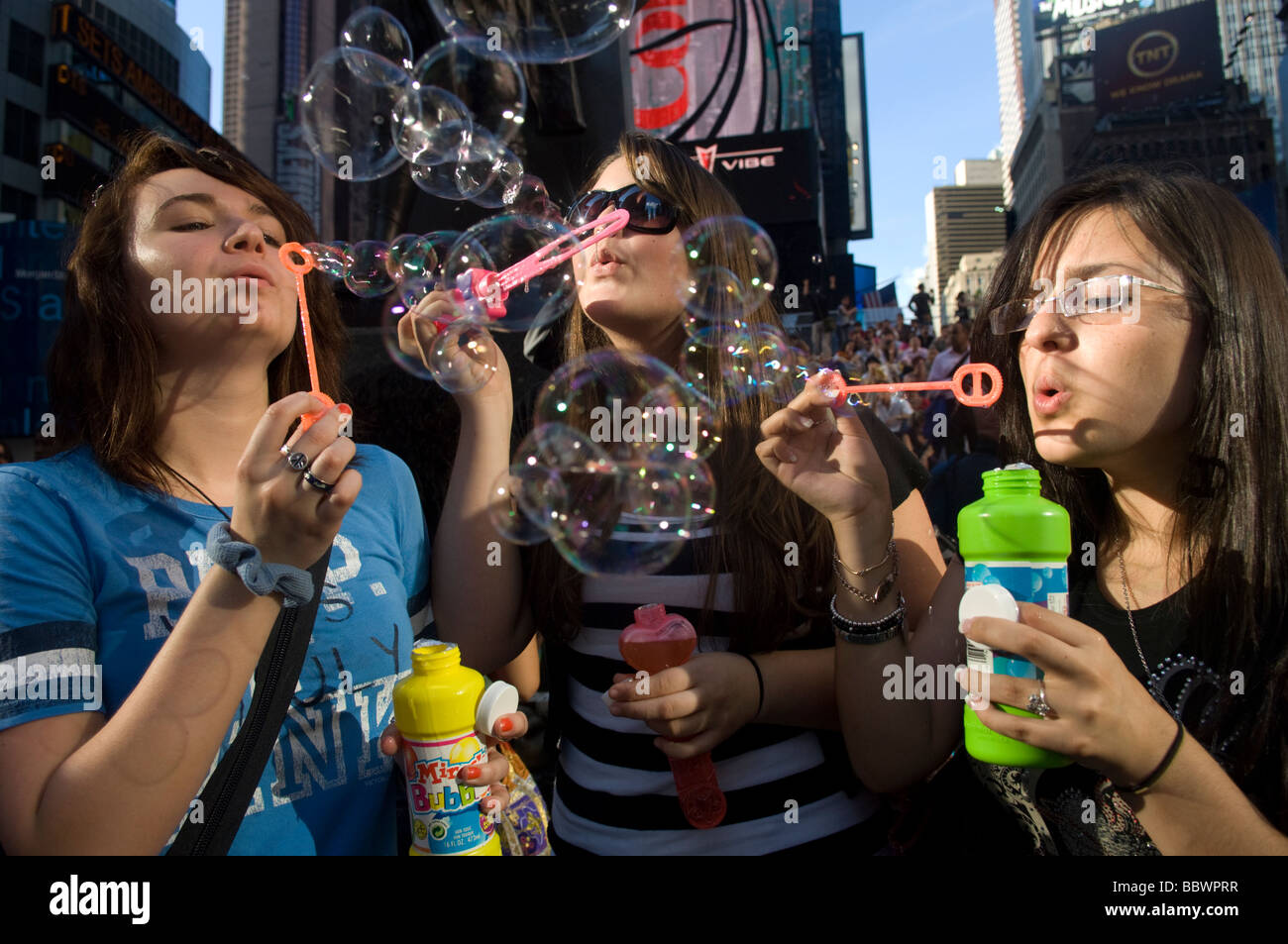 Hundreds of people gather in Times Square in New York to launch millions of bubbles - Stock Image