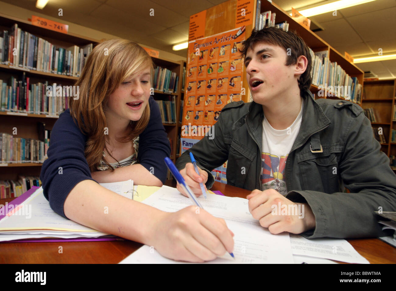 Students talking and working in school library in preparation for A Levels. They are both 17-18 years old. - Stock Image