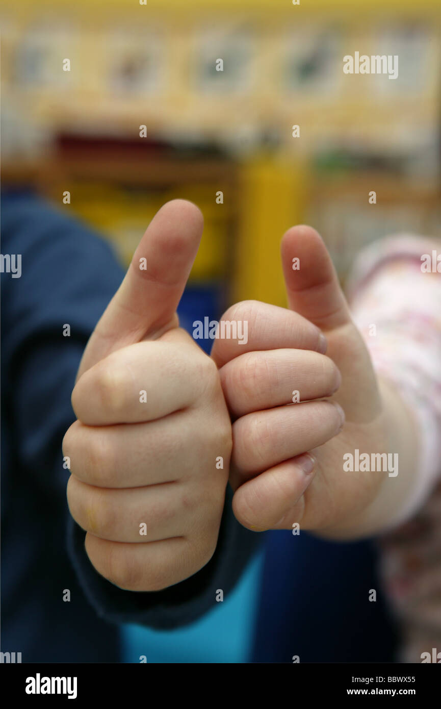 two children's hands striking a thumbs up ok sign with schools background - Stock Image