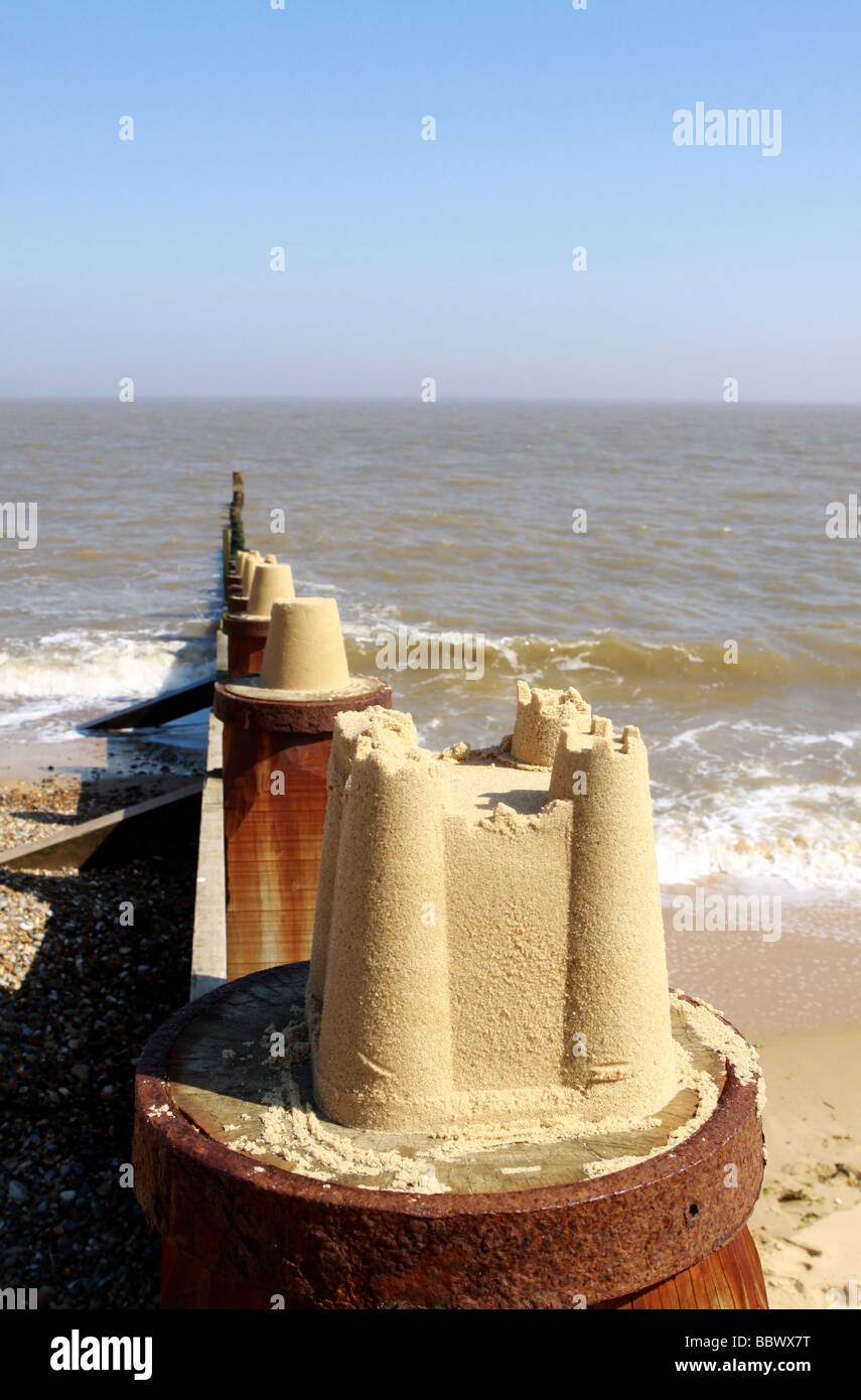 English summer holidays illustration or concept showing sand castles placed on top of groyne Stock Photo