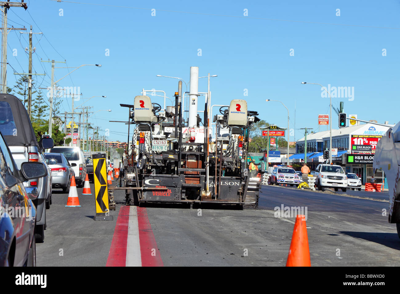 Traffic chaos as roadway is paved during peak hour using machinery and trucks - Stock Image