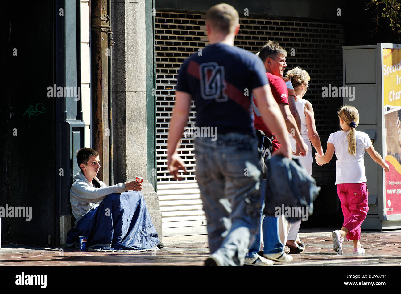 People passing young man begging in the streets of central Dublin Republic of Ireland - Stock Image