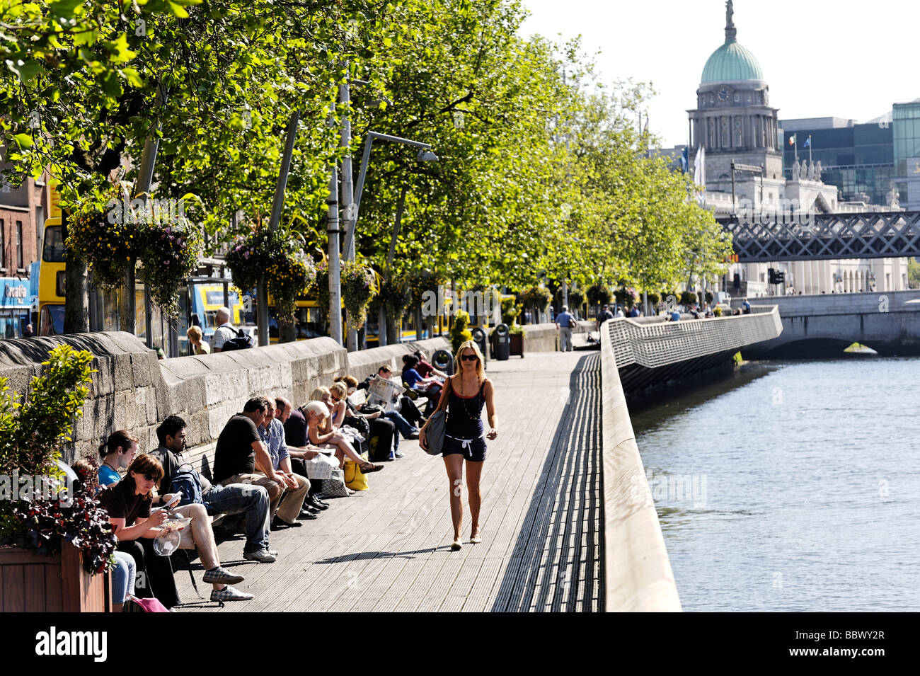 People sitting in the sun on the Liffey boardwalk on Lower Ormond Quay Central Dublin Republic of Ireland - Stock Image