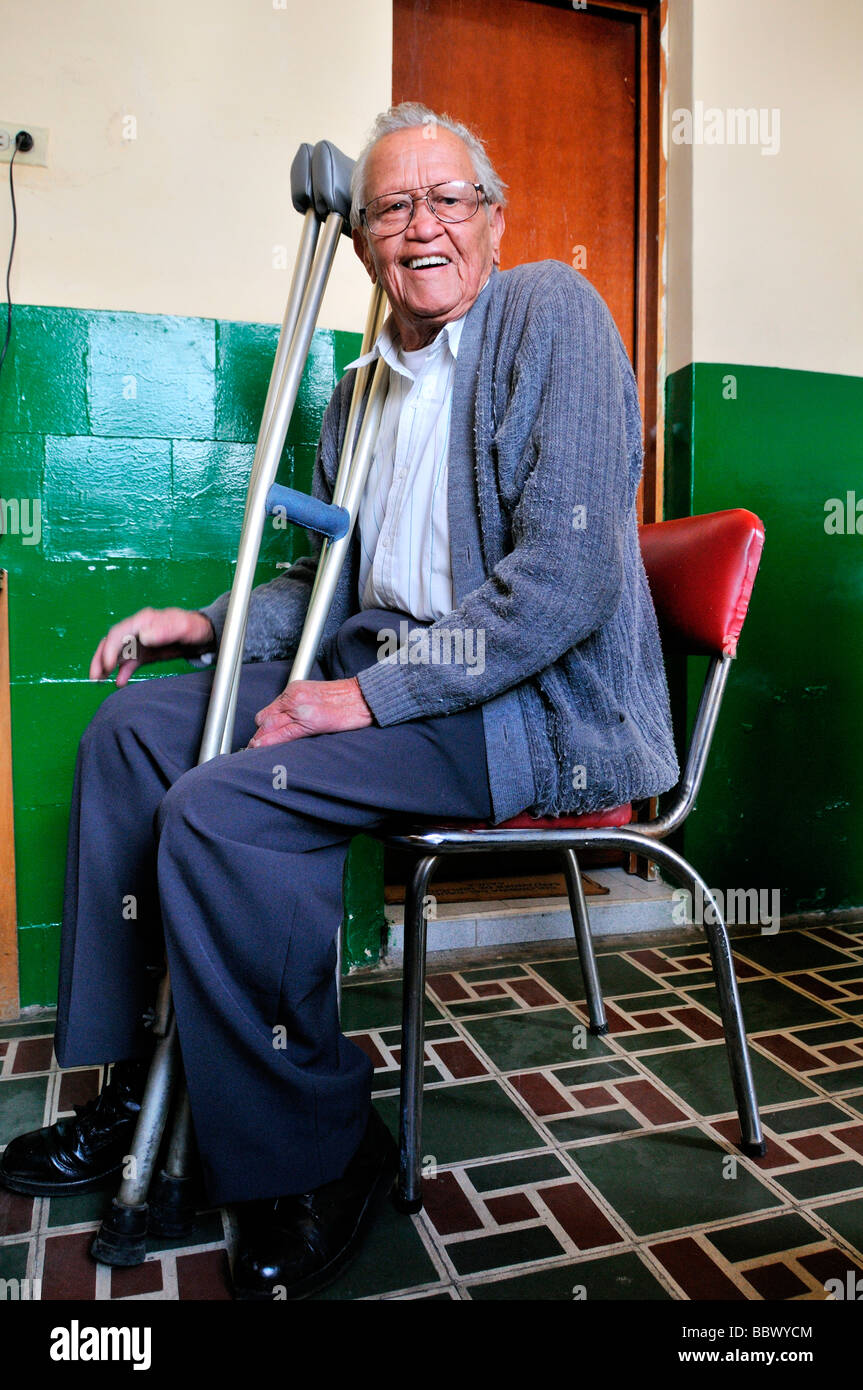 Leprosy patient with crutches, 77 years, in the ASOHAN, a self-help organization for leprosy sufferers, Bogota, - Stock Image