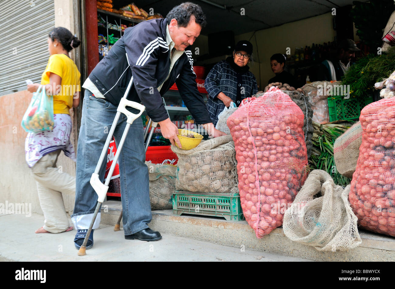 Leprosy patient with crutches shopping in a grocery store, Bogota, Colombia, South America - Stock Image