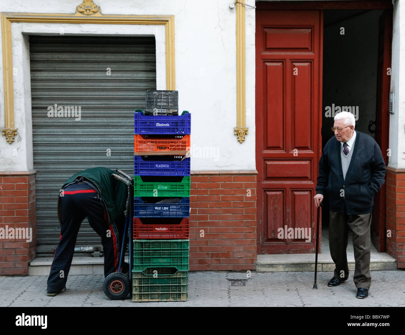 elderly man watches young man handle empty crates in Sevilla Andalucia Spain - Stock Image