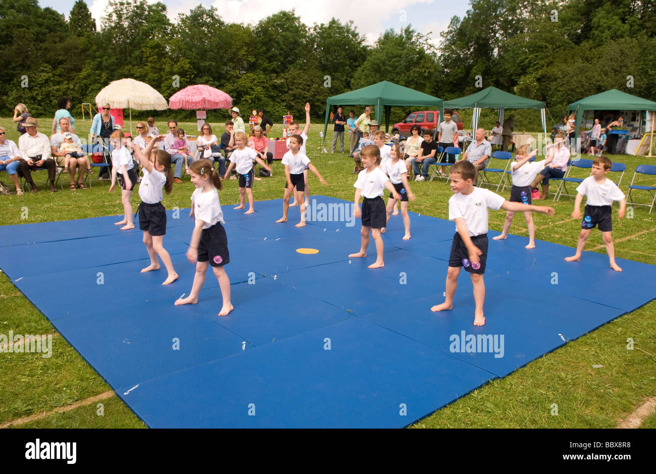 Key stage 1 gym club giving a demonstration at a school summer fete, Medstead, near Alton, Hampshire, UK. - Stock Image