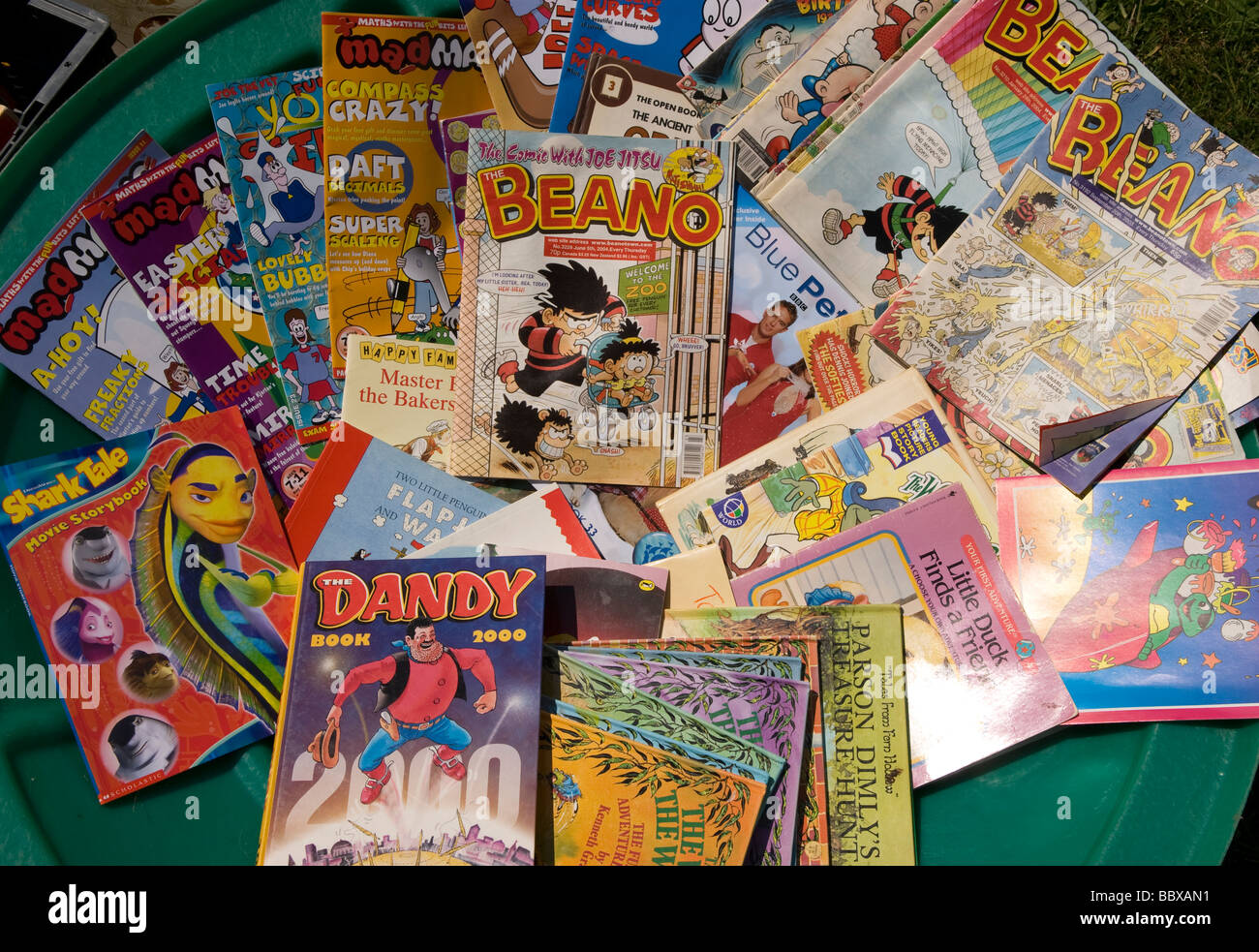 Display of traditional comics on sale at a school summer fete, Medstead, Alton, Hampshire, UK. - Stock Image