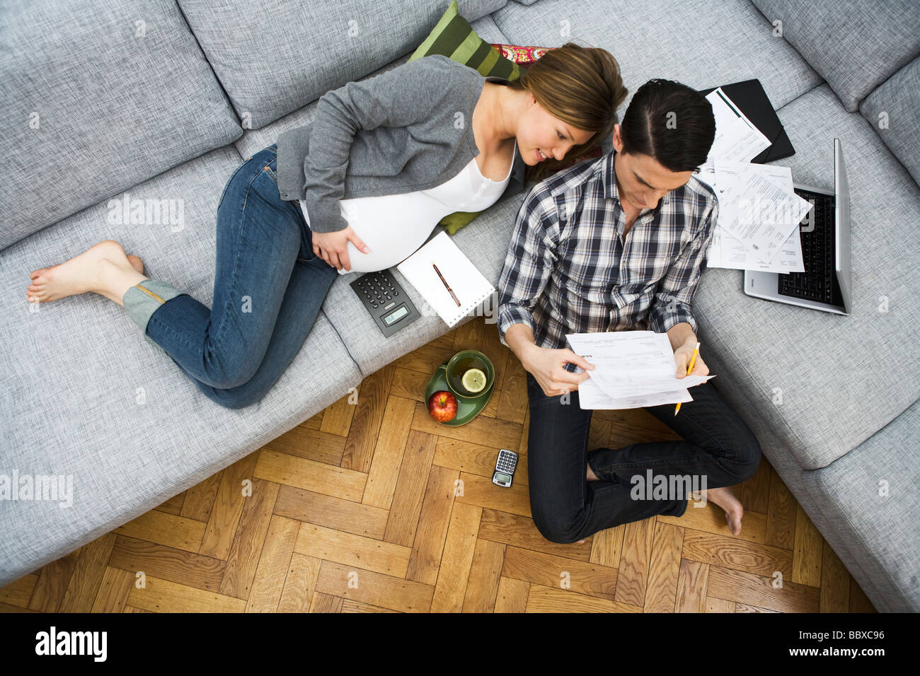 A pregnant woman and a man discussing their home finances Sweden. - Stock Image