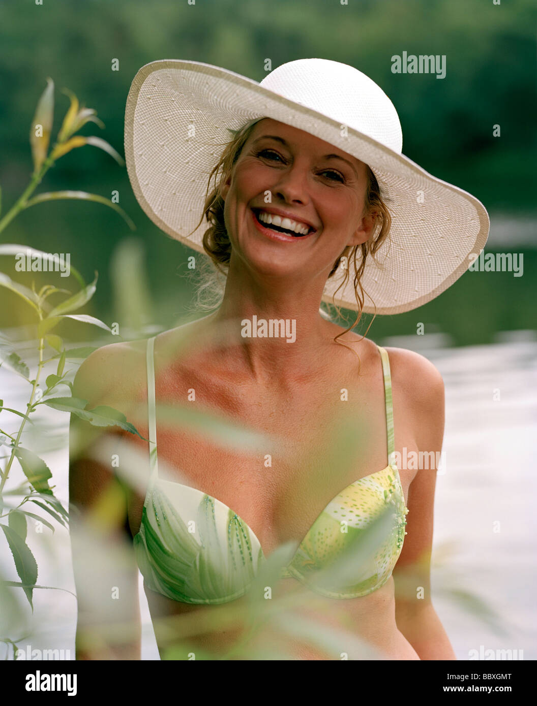 A smiling woman wearing bikini and a hat Sweden. - Stock Image