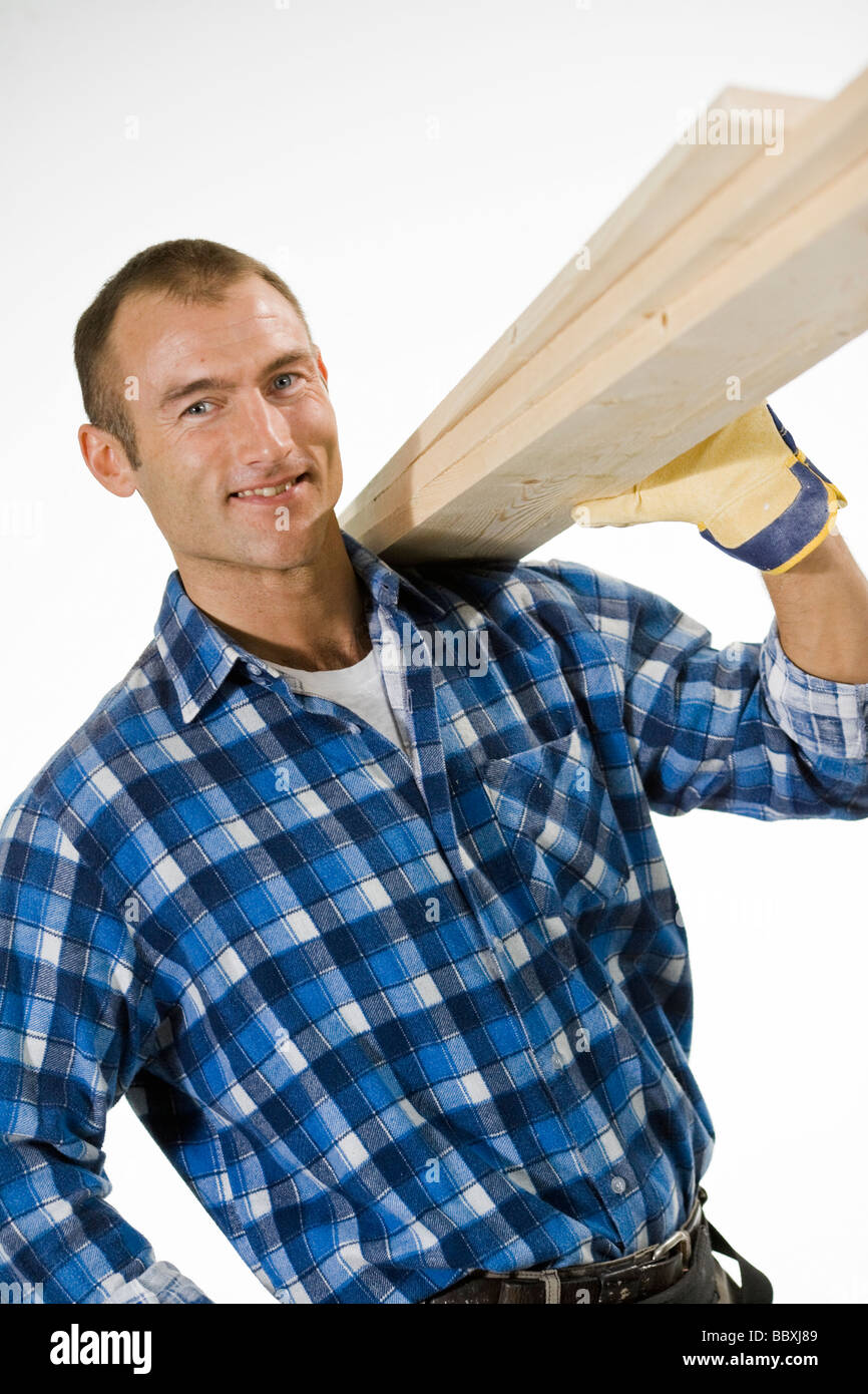 A carpenter carrying planks. - Stock Image