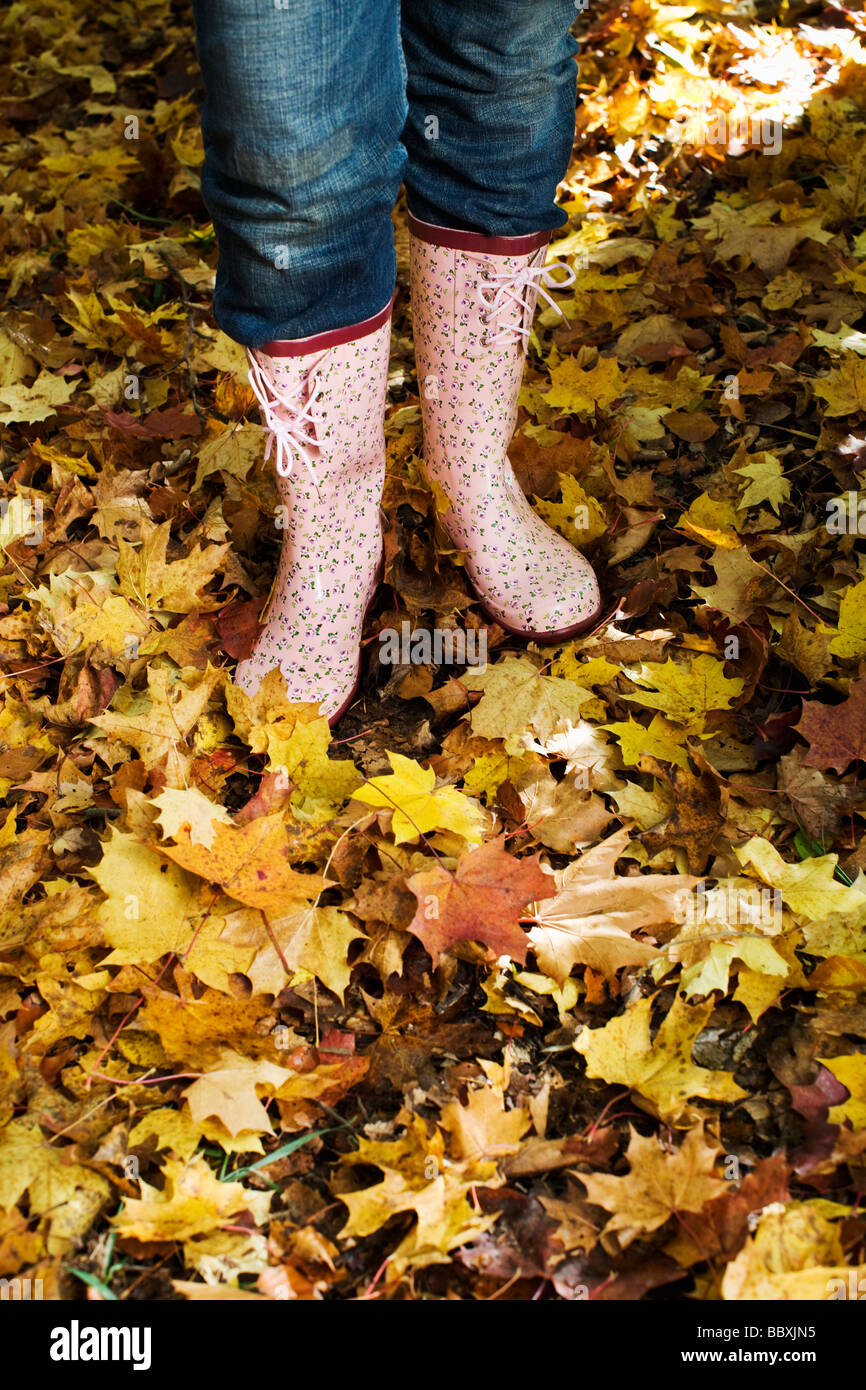 A woman wearing rubber boats in autumn forest Stockholm Sweden. Stock Photo