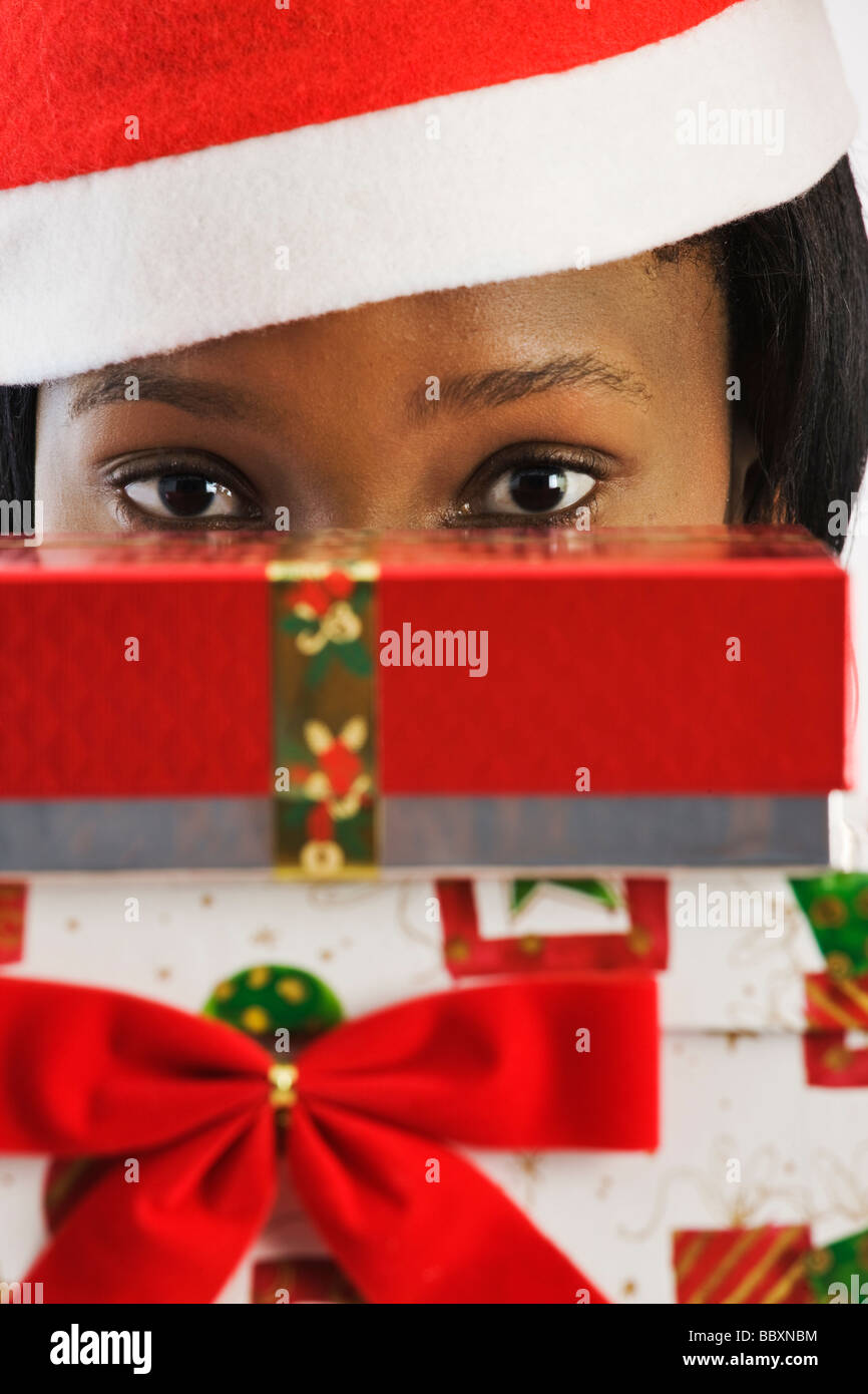 African woman wearing Santa suit peeking over Christmas gifts - Stock Image