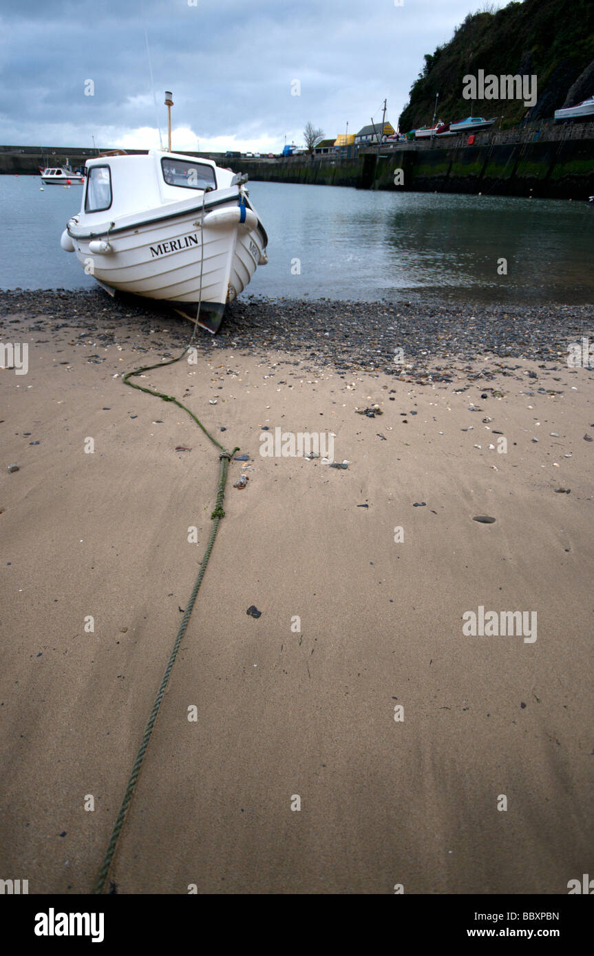 A small boat called merlin  at Saundersfoot harbour at low tide on an overcast day in winter with little or no tourism. - Stock Image