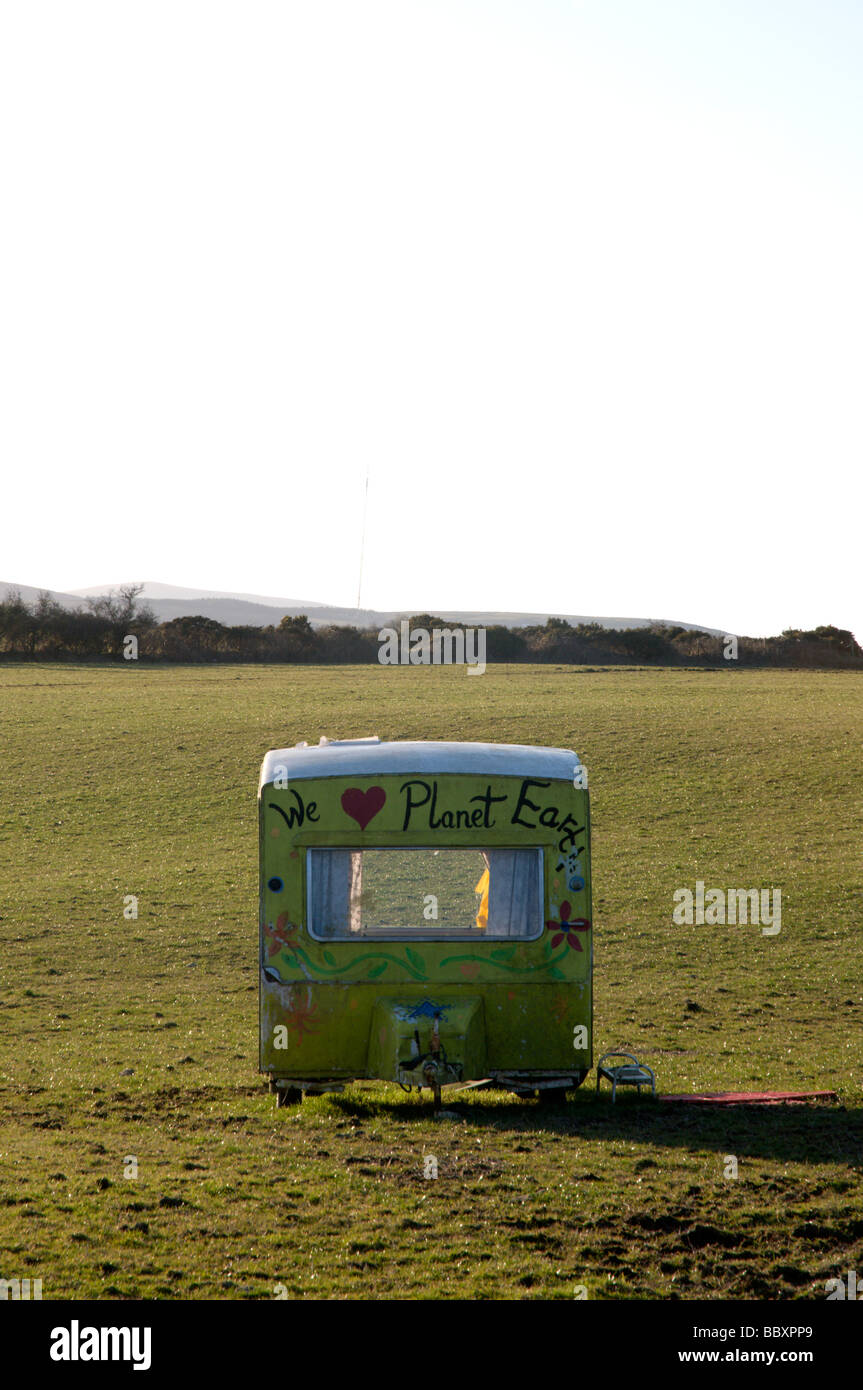 Hippy Caravan in field with we love planet earth written on the front to promote enviromental issues, - Stock Image