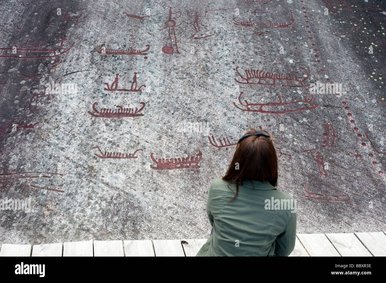 Woman looking at ancient Bronze Age rock carvings at Vitlycke on Tanum plane in Sweden - Stock Image
