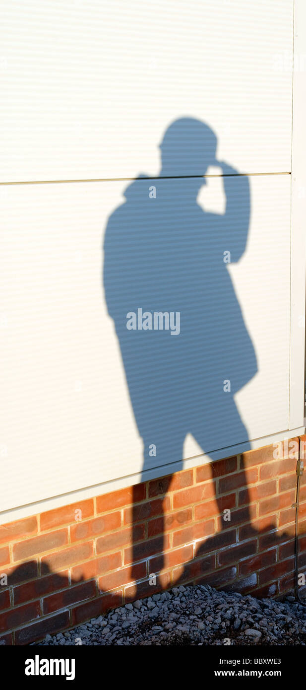 shadow of a builder against a wall on a building site - Stock Image