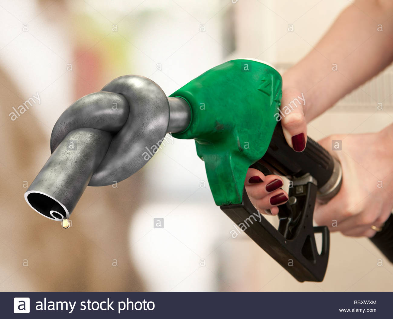 close up of a woman's hands holding a petrol pump with a knot in the nozzle. - Stock Image