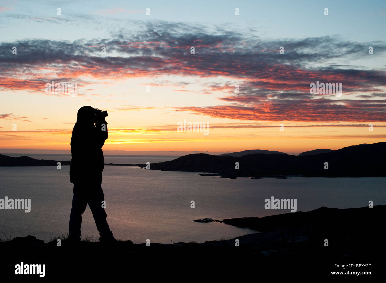 Silhouette of a photographer at sunset looking over Taransay Island, Isle of Harris, Outer Hebrides, Scotland - Stock Image