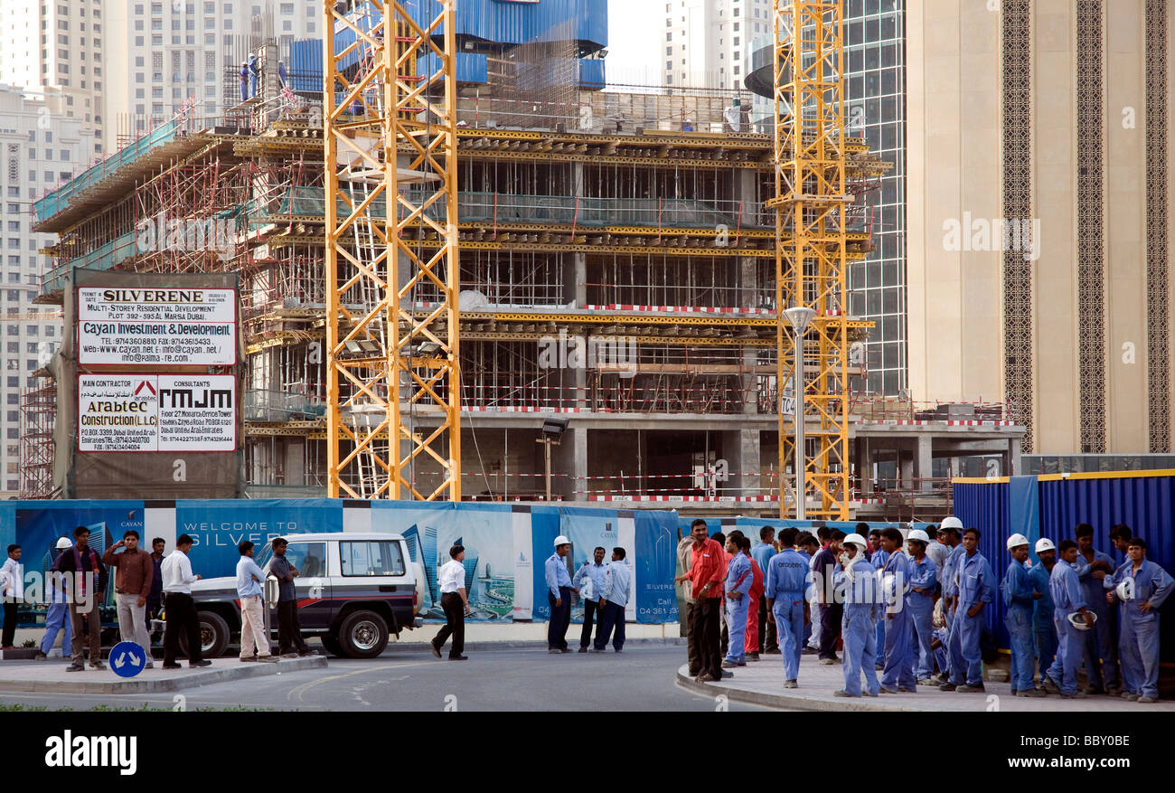 In Dubai construction workers wait at day's end for transport to their dormitories - Stock Image