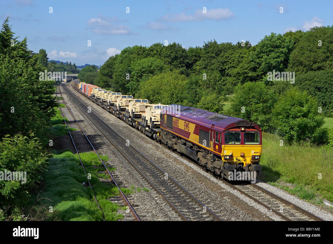 A DBS Class 66 hauls a MoD train through Cheltenham. The wagons at the front are carrying brand new Mastiffs for - Stock Image