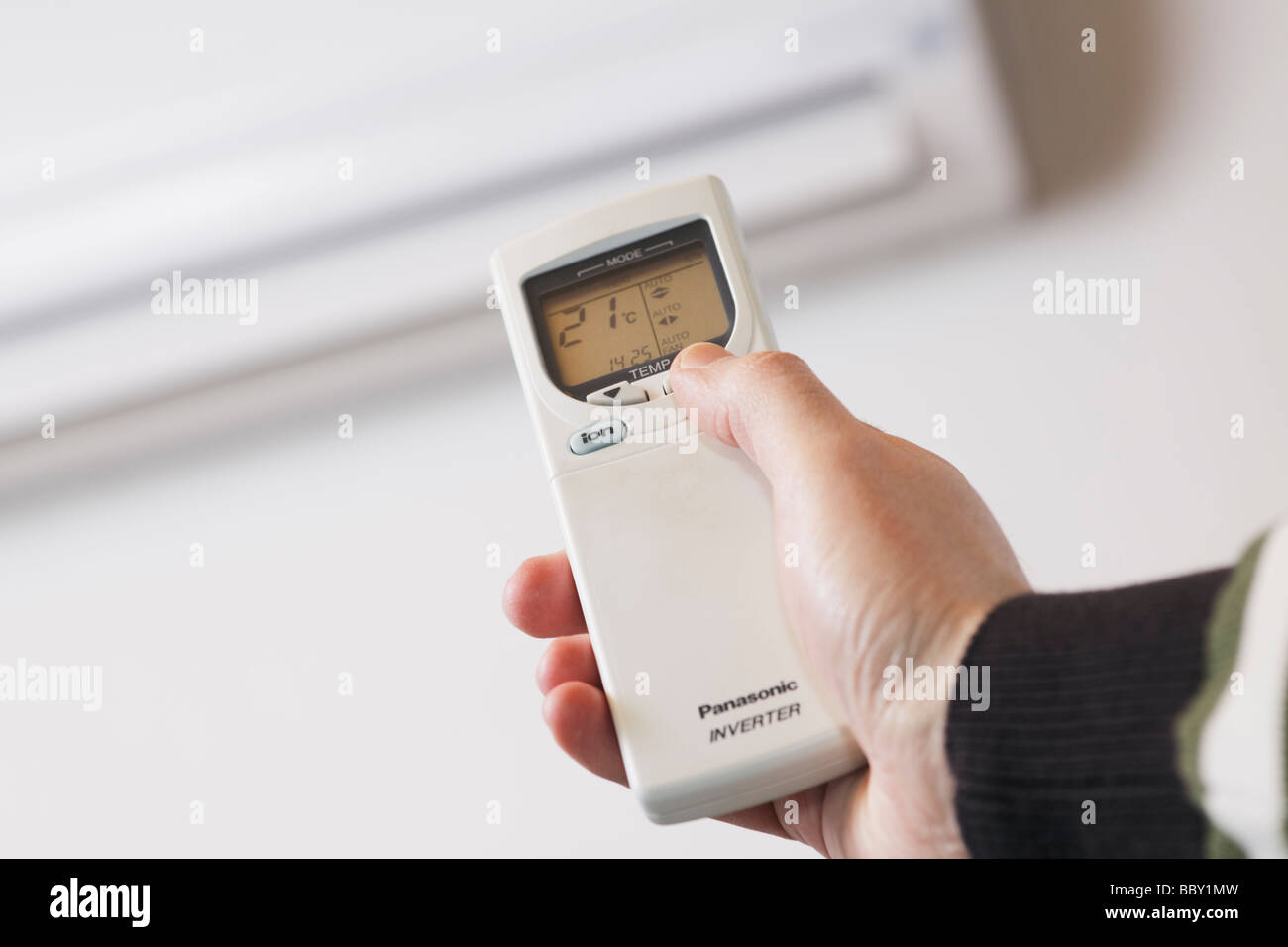 Hand using remote control of a reverse cycle air conditioner heat pump seen in background - Stock Image