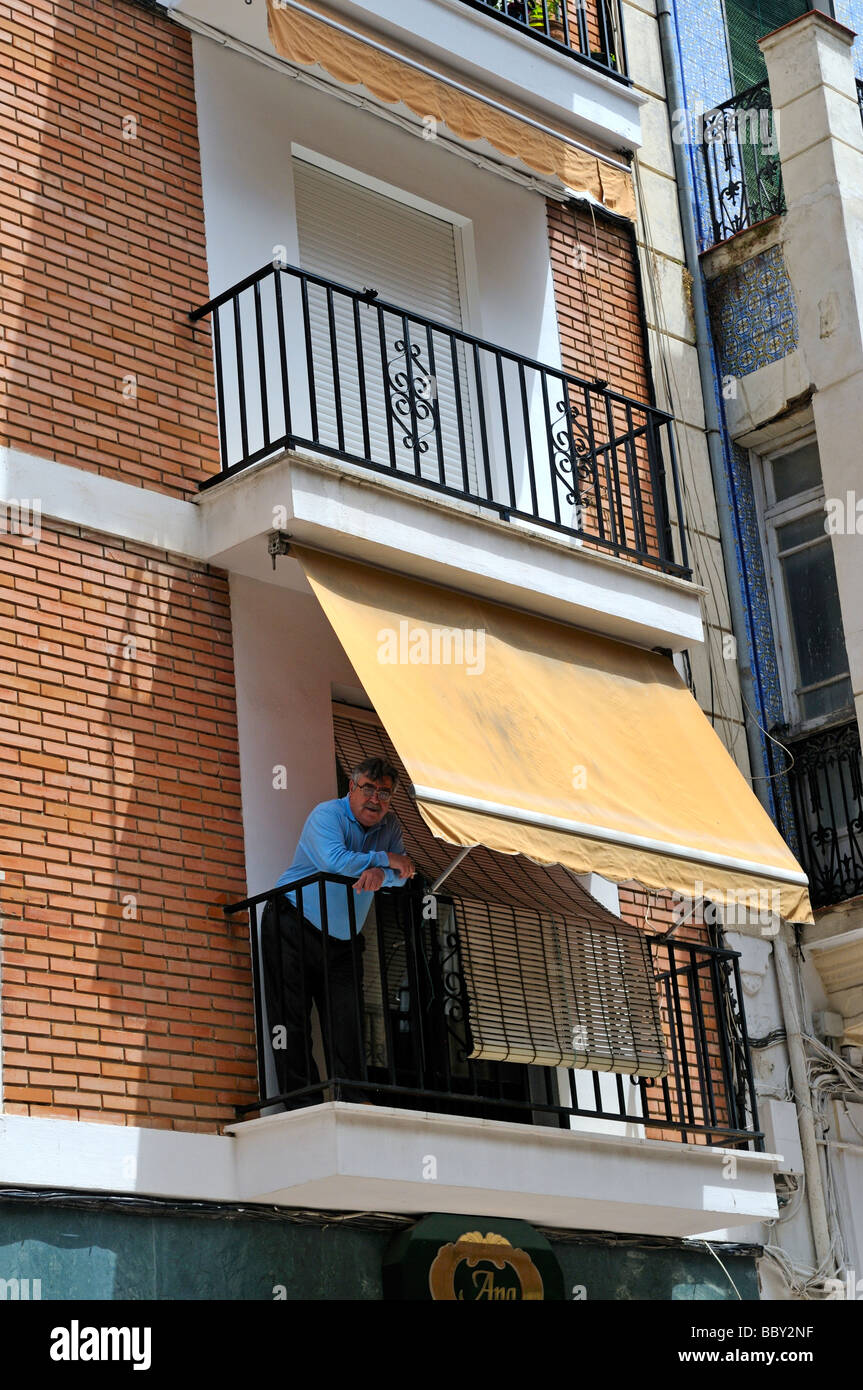 Man standing on balcony with awning in Antequera Andalucia Spain - Stock Image