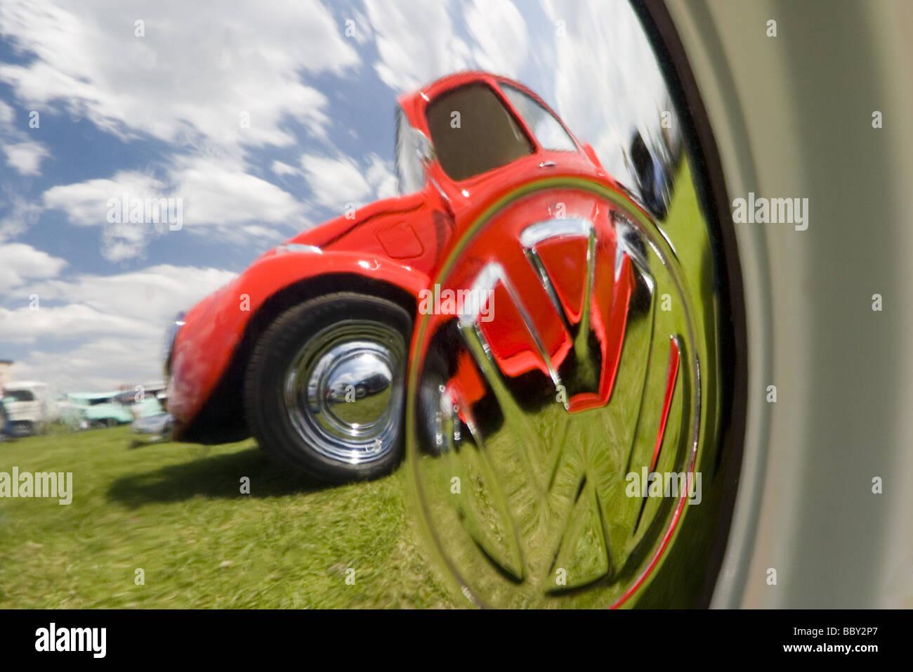 Orange Volkswagen Beetle reflected in chrome VW hub cap - Stock Image