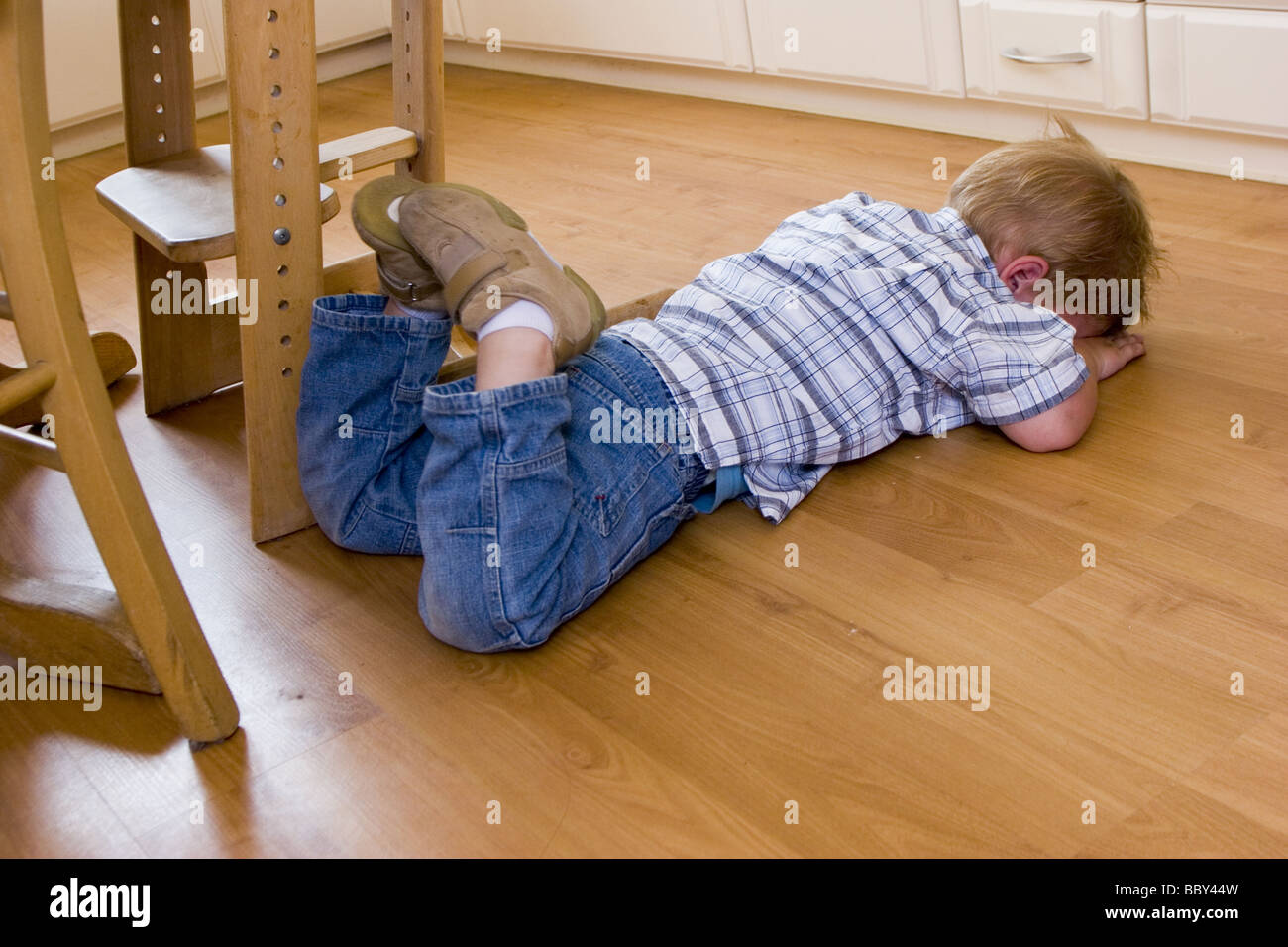 Little child throwing a temper tantrum at home. The toddler is down on the floor, hiding his face, out of control - Stock Image