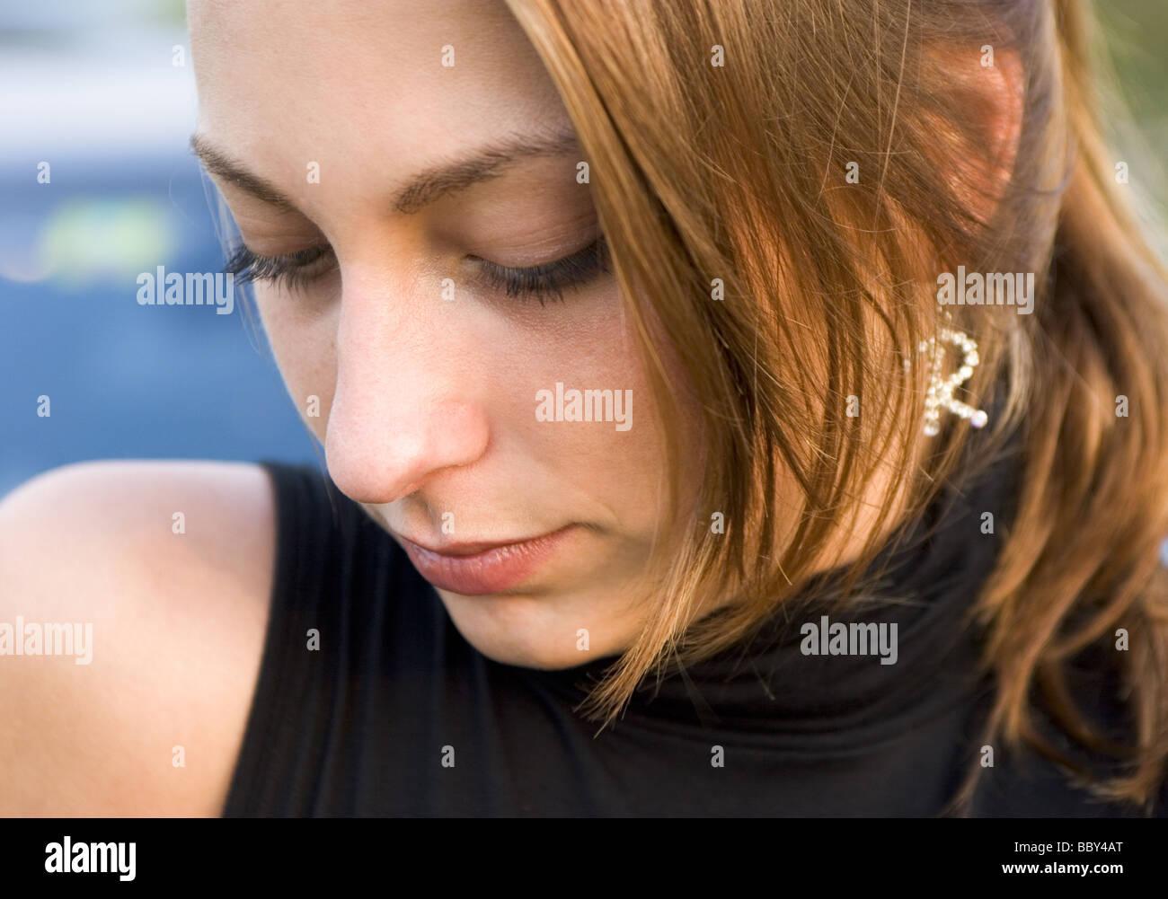 Upset teenage girl looking down - Stock Image