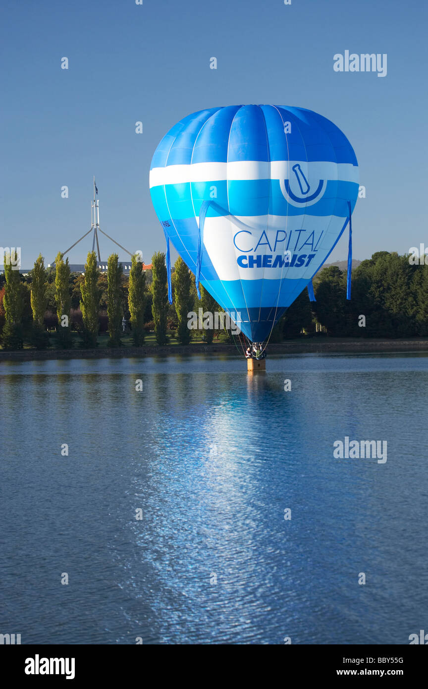 Hot Air Balloon Touching Down on Lake Burley Griffin and Flagpole on Parliament House Canberra ACT Australia - Stock Image