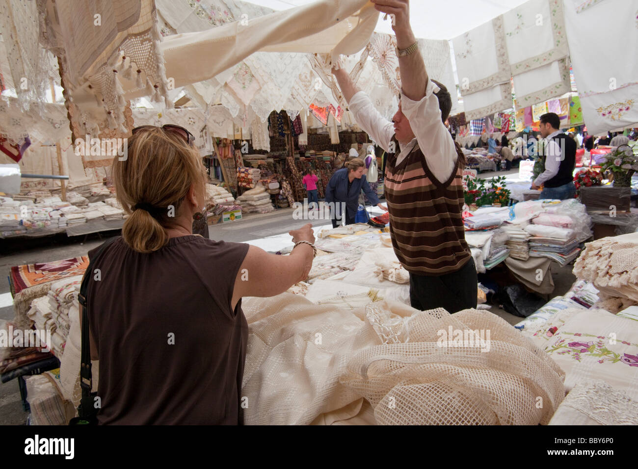 Woman bargaining for a tablecloth in a marketplace in western Turkey - Stock Image