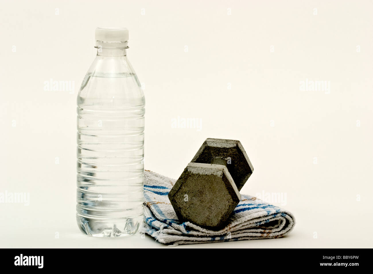 A dumbbell on a sweat towel next to a bottle of water - Stock Image