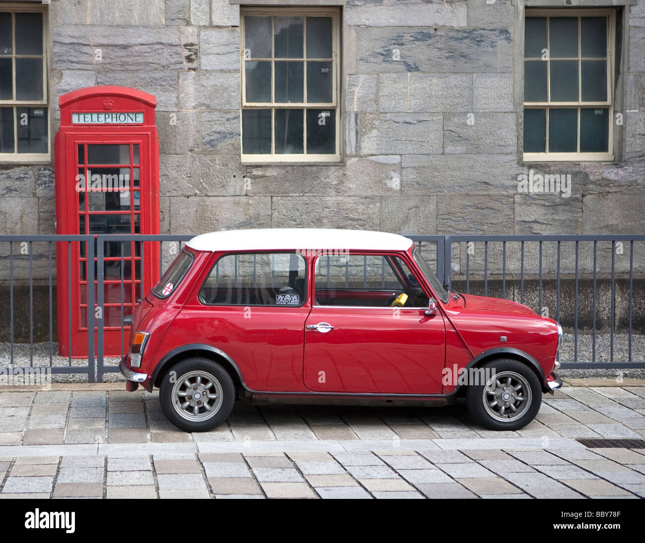 red Austin Cooper mini car parked in front of red telephone box. Royal William Yard, Plymouth, Devon, England, UK - Stock Image