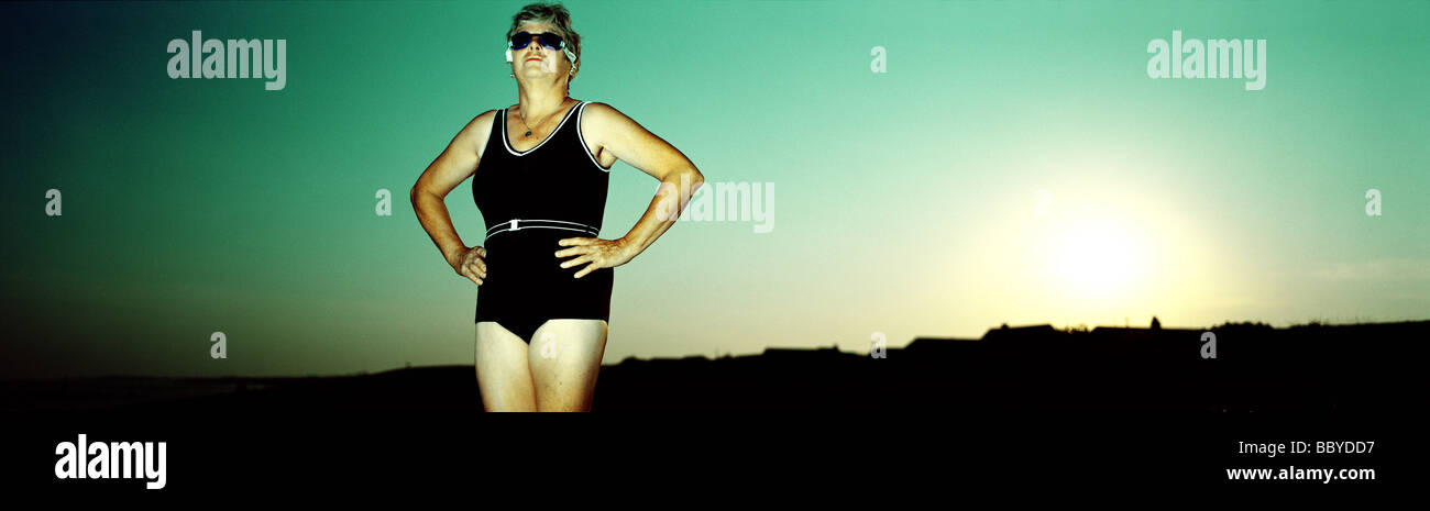 Mature woman in swimming costume at sunset - Stock Image