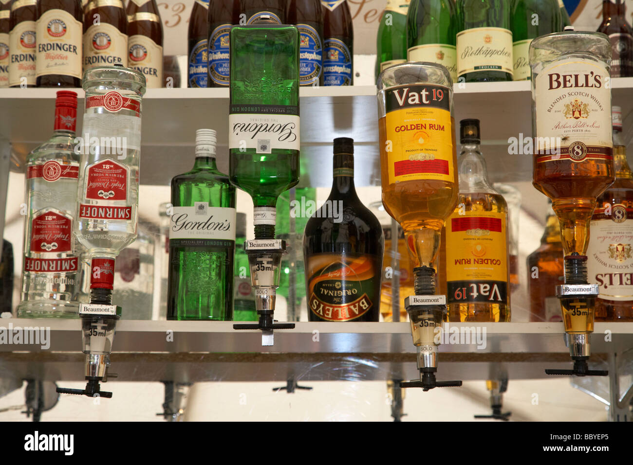 row of alcoholic spirits and bar optics in a bar pub in ireland - Stock Image