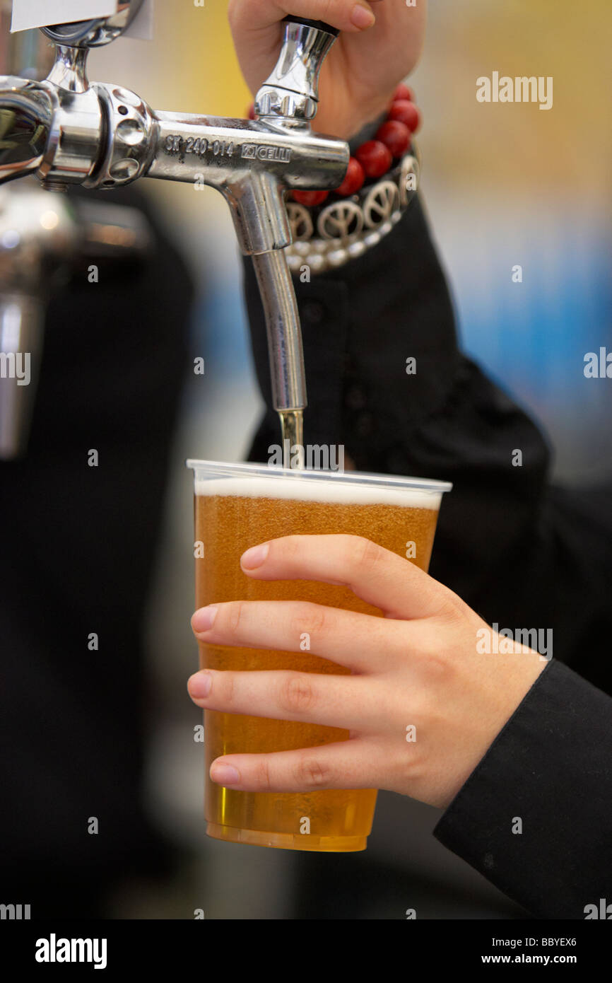 female barmaid pouring a pint of beer into a plastic glass in a beer tent at a festival - Stock Image