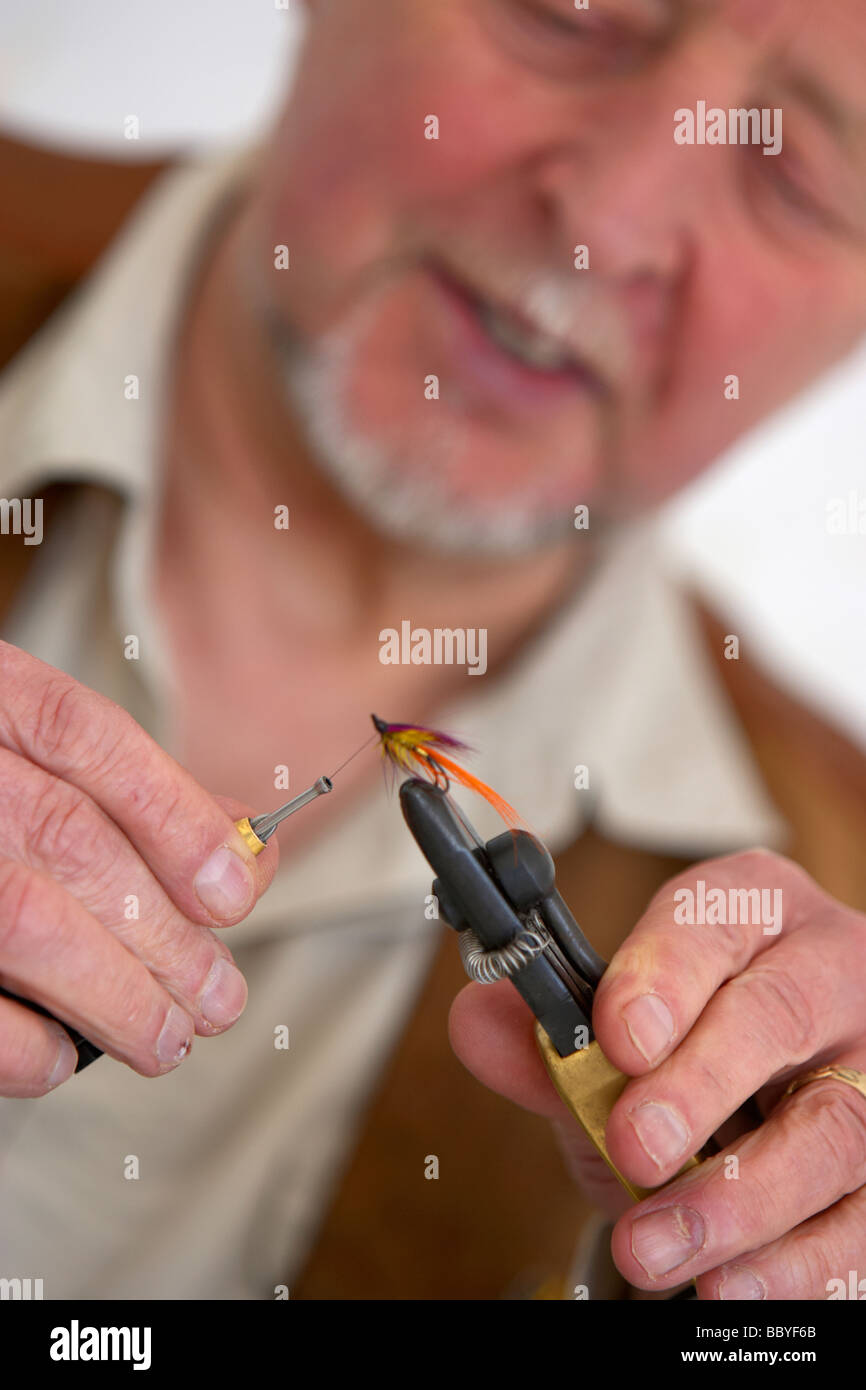 man fly tying with fly in vice uk - Stock Image