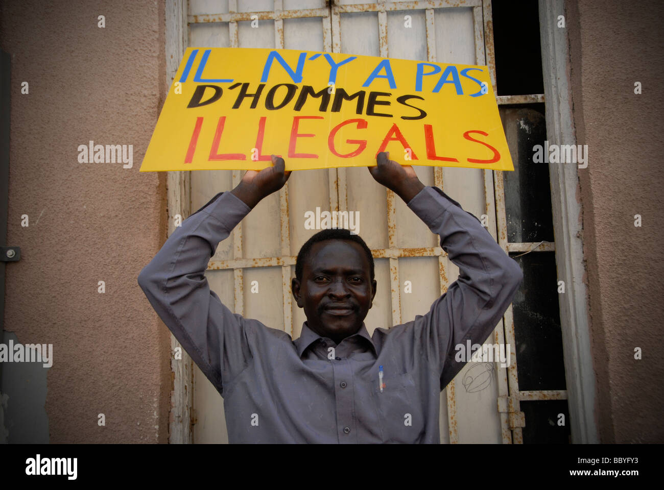 An African migrant holds a placard in French which reads 'There are no illegal humans' during a demonstration - Stock Image