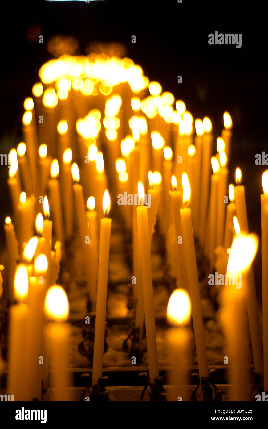 Votive candles burning in a church - Stock Image