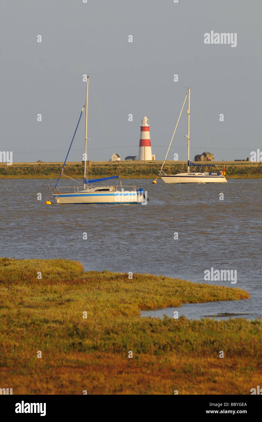Sailing Boats moored on River Ore and  Lighthouse in background at Orford Suffolk - Stock Image
