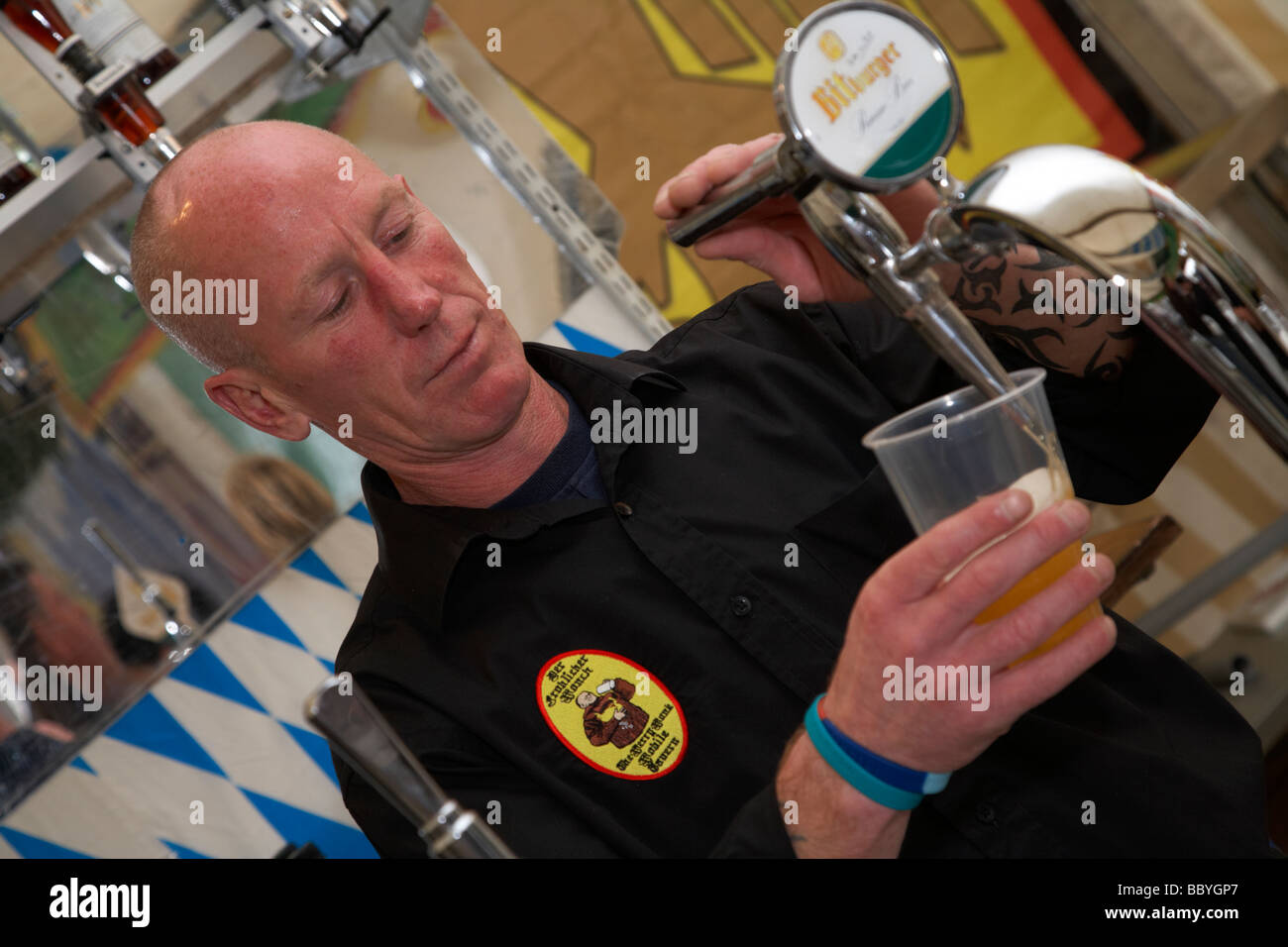 barman pouring a beer into a plastic cup in an imitation german beer stall in the uk - Stock Image